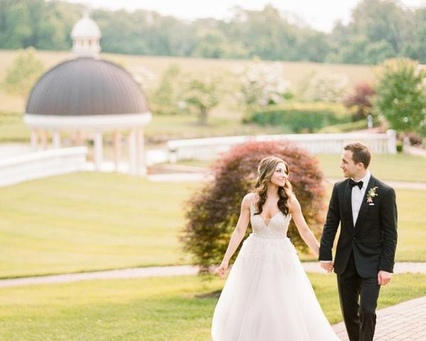 Bride and Groom walk along path at their Ashford Estate Wedding. Photo by Rebecca Yale. Shared on Flutter Social by The Styled Bride.
