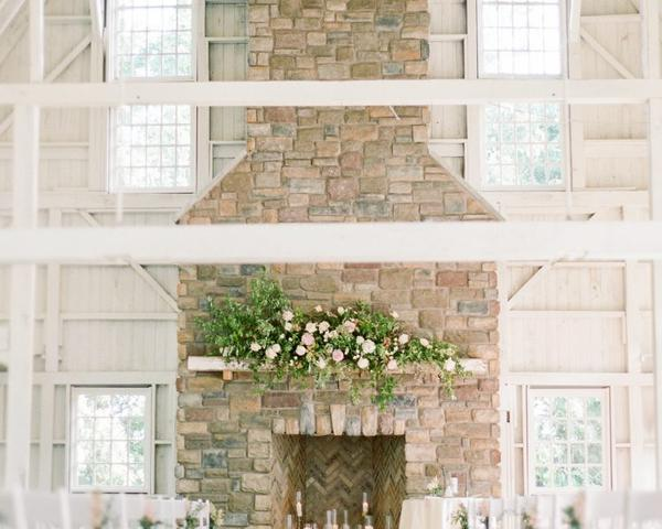 Candlelit and flower covered barn fireplace ceremony space at Ashford Estate. Photo by Rebecca Yale. Shared on Flutter Social by