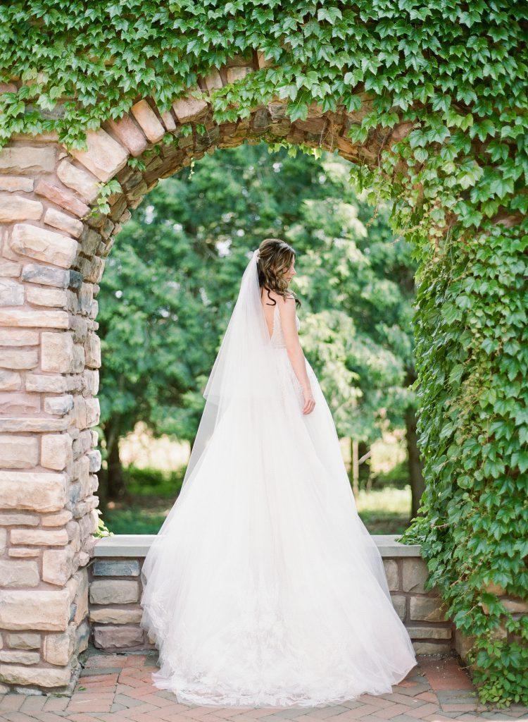 Bride in ballgown and cathedral veil under stone arch at Ashford Estate Wedding