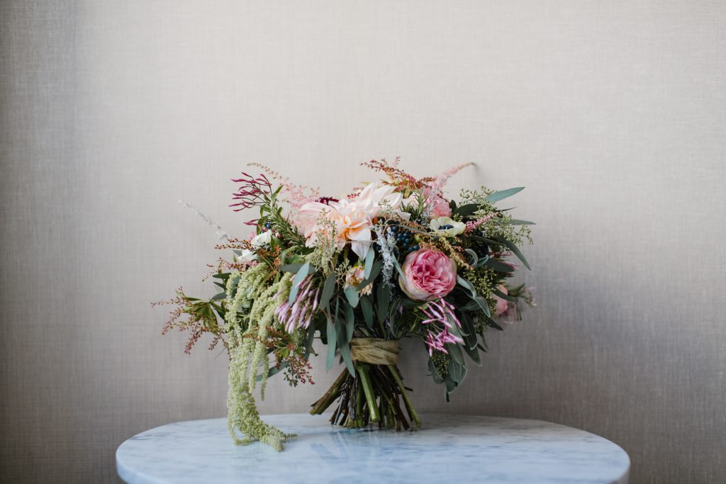 Wild wedding bouquet with pink, blue, and maroon flowers. Wedding photo by Love Me Do Photography.