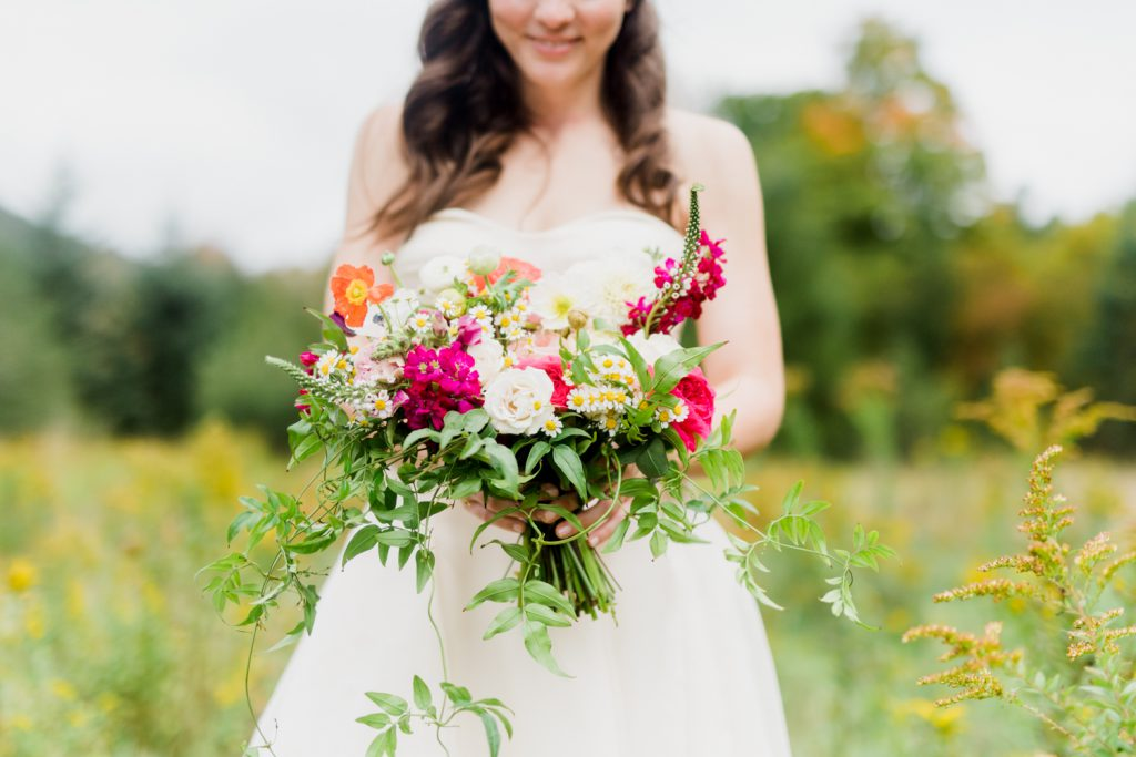Bride holding bright wildflower inspired bouquet at Catskills Wedding