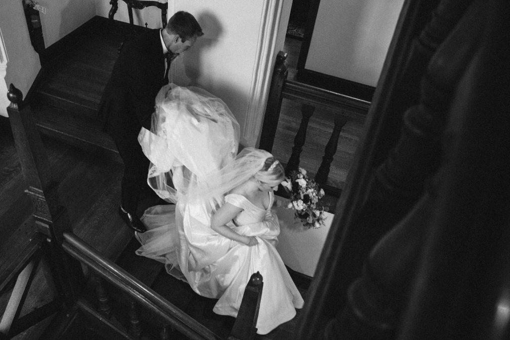 Aldie mansion groom helps bride down the stairs
