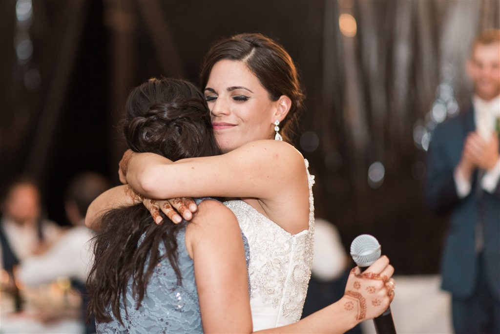 bride hugs maid of honor after speech greenville country club wedding