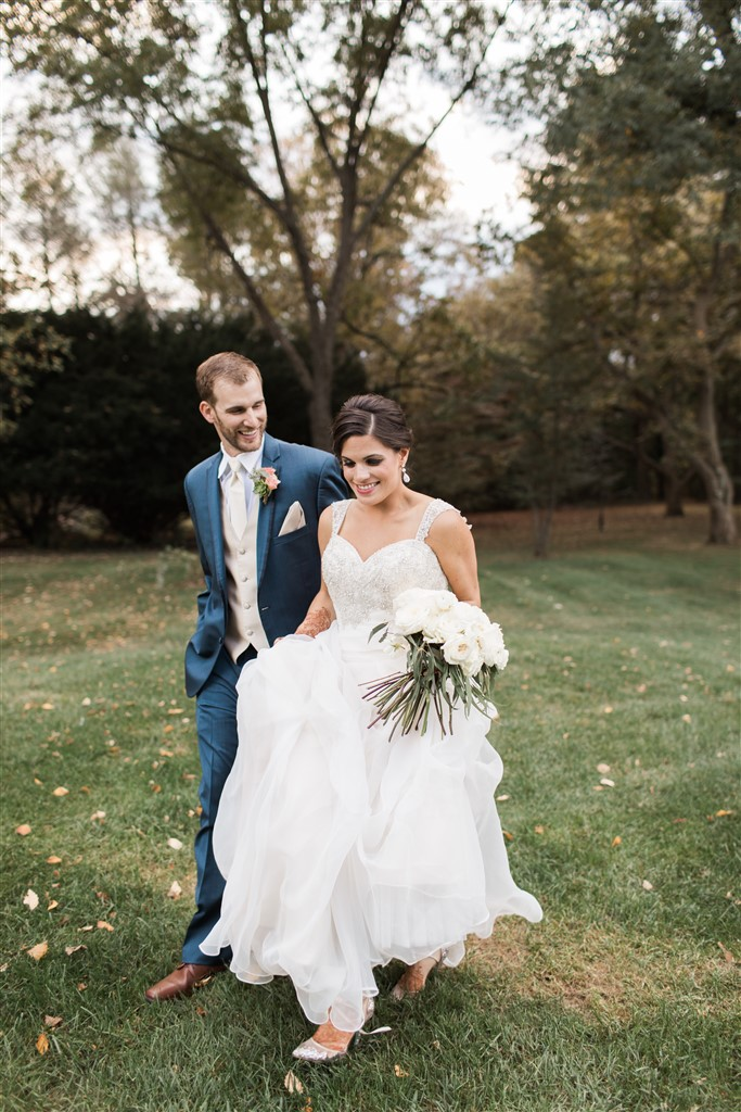 bride and groom walking with bouquet by fresh designs florist photo by samantha jay photography