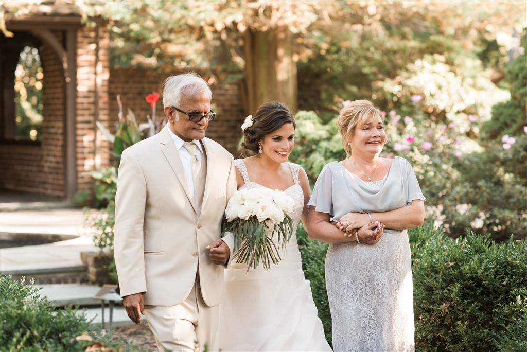 bride walks down aisle with parents carrying gorgeous bouquet by fresh designs florist