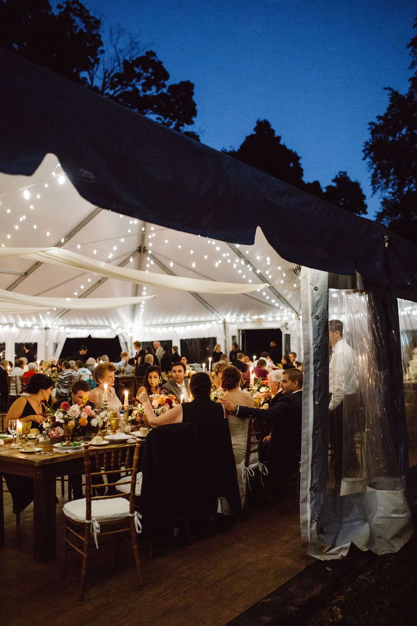Dinner at farmhouse tables under a lighted tent at Ridgeland Mansion Philadelphia Wedding. Photo by Ali & Paul Co.