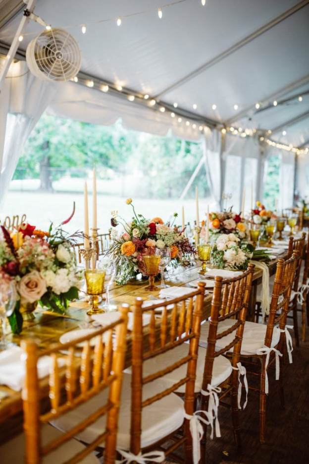 Tablescape with fall flower centerpieces, vintage glassware, and candlesticks on farmhouse table at Ridgeland Mansion Philadelphia Wedding