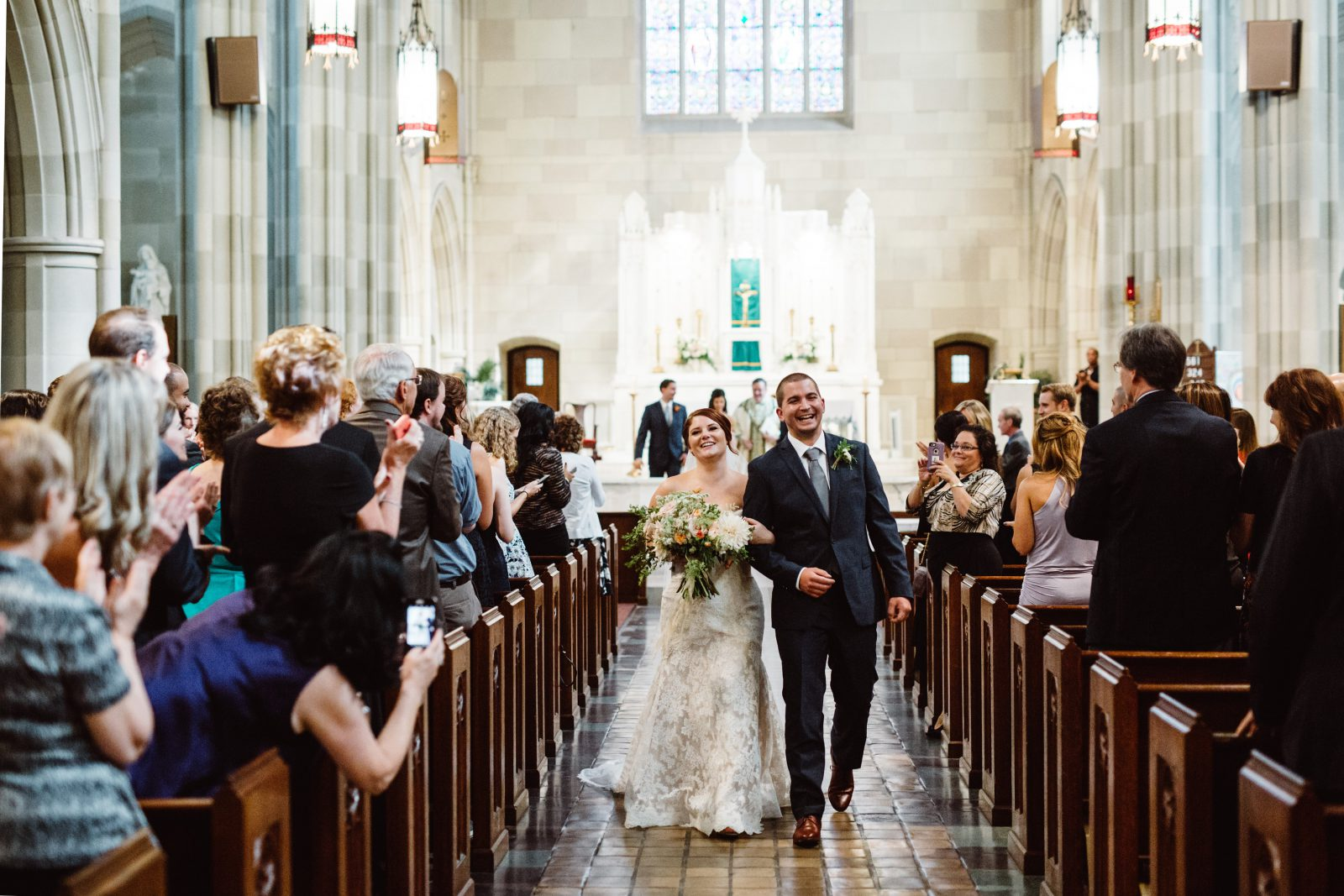Bride and groom walk down the aisle after wedding ceremony at Saint Coleman's Church. Bouquet by Fresh Designs Florist. Photo by Ali & Paul Co.