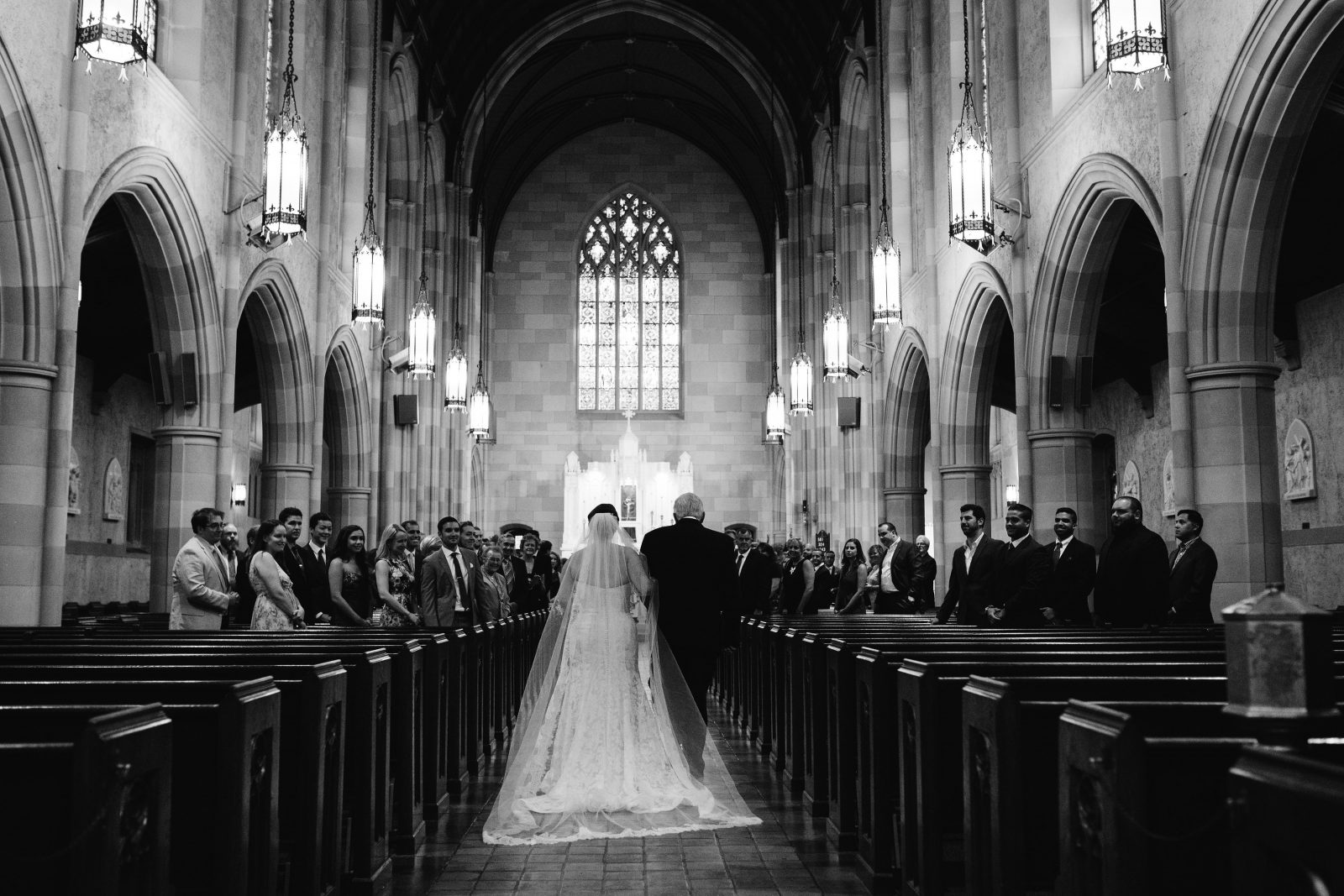 Back view of bride in cathedral veil and her father walking down aisle in Saint Colemans Church before wedding reception at Ridgeland Mansion Philadelphia. Photo by Ali & Paul Co.