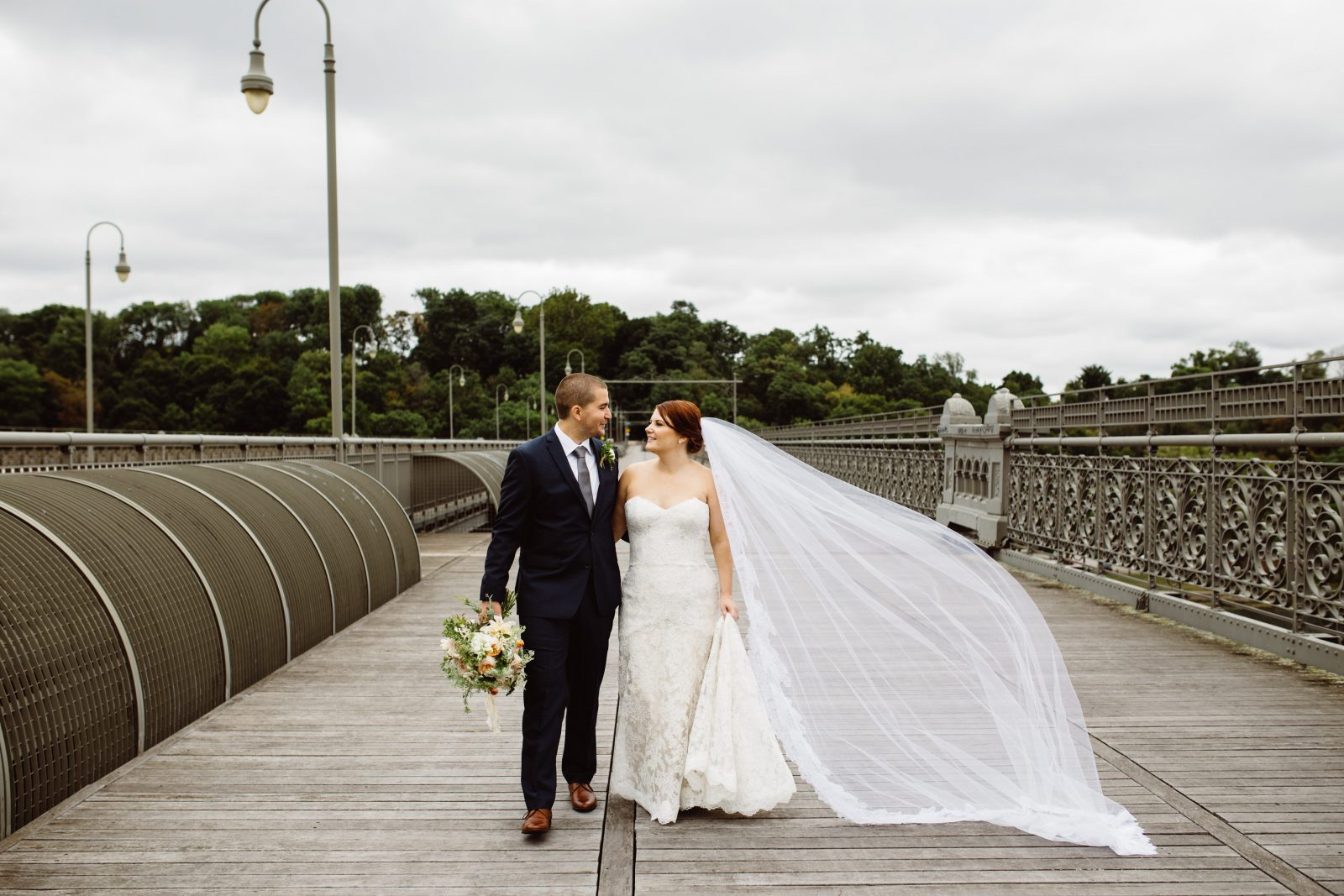 Bride in lace gown and cathedral veil on bridge with groom at Ridgeland Mansion Wedding. Bouquet by Fresh Designs Florist. Photo by Ali & Paul Co.