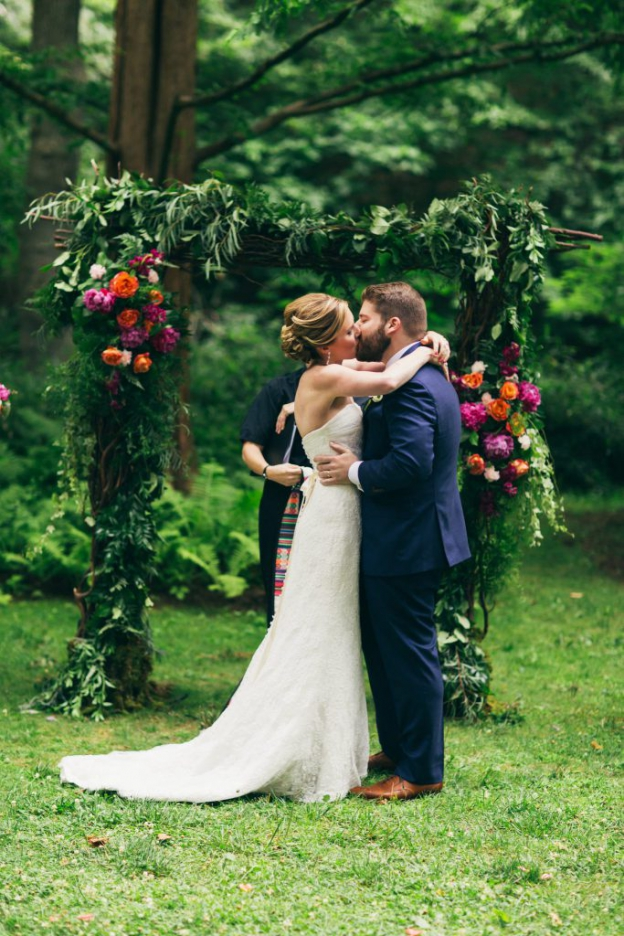 Bride and groom kiss in front of gorgeous floral arch at wedding at The Old Mill