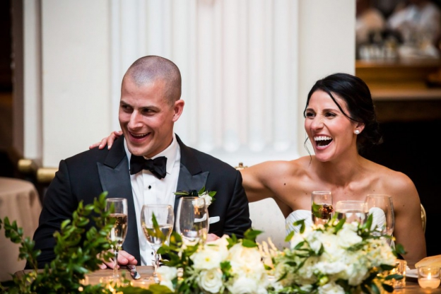 Bride and groom laugh during speeches at wedding at Ballroom at the Ben