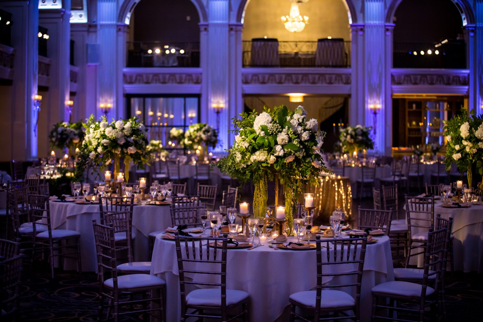 Candlelit round tables with tall white floral centerpieces at Ballroom at the Ben Wedding