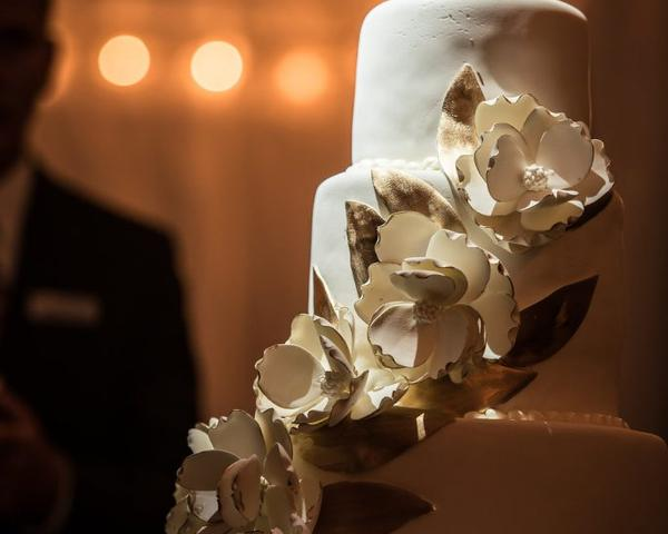 Four-tier white fondant wedding cake with gold-brushed white sugar flowers by L'Estis Desserts at Greystone Hall Wedding. Photo by Christie Green Photography