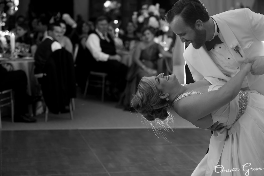 Groom dips bride during first dance at classically elegant tented Greystone Hall wedding reception. Photo by Christie Green Photography