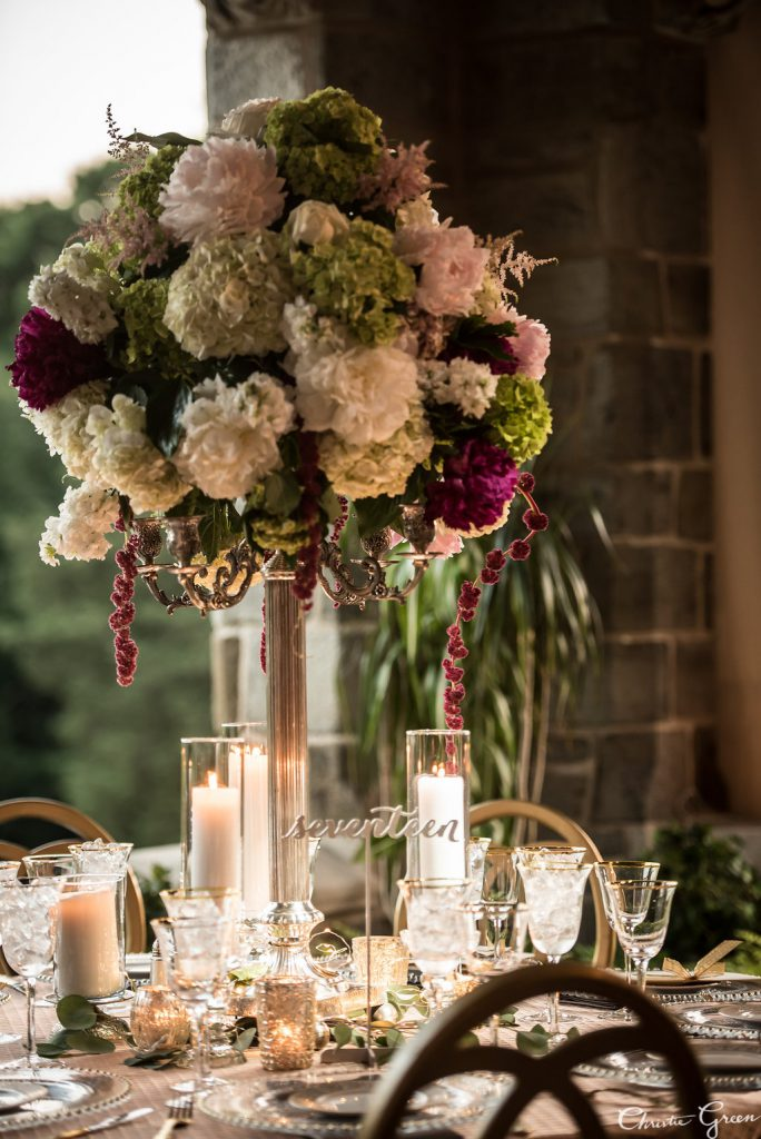 Tall Floral Centerpieces with pink, burgundy, and ivory flowers by Roberston's Flowers surrounded by candles at Greystone Hall wedding. Photo by Christie Green Photography