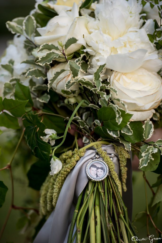 Gorgeous white and green bridal bouquet by Robertson's Flowers accessorized with a photo charm of the bride's grandparents. Photo by Christie Green Photography