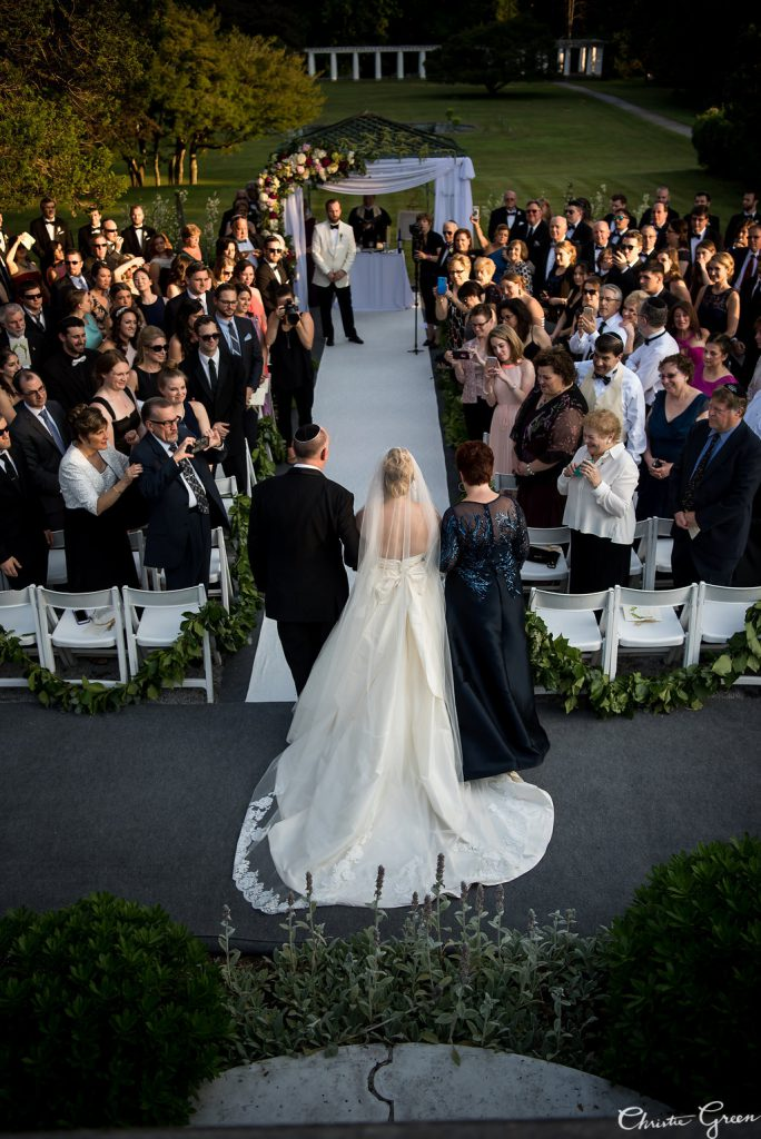 Bride in Modern Trousseau gown begins to walk down the aisle during gorgeous outdoor summer wedding ceremony at Greystone Hall. Photo by Christie Green Photography