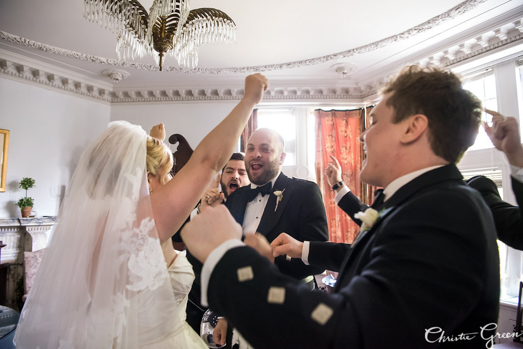 Bride celebrates with her best men before Greystone Hall Wedding ceremony. Photo by Christie Green Photography