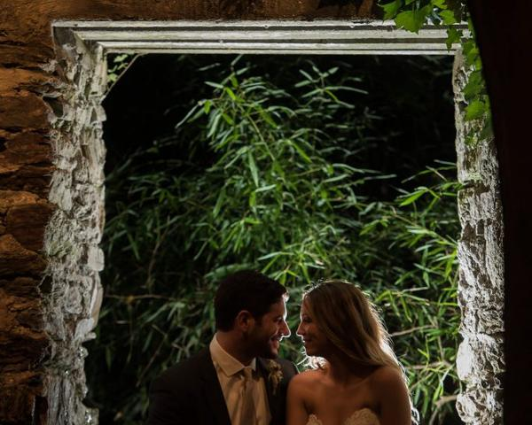 Backlit bride and groom sit in a window of the stone ruins at their Old Mill Wedding. Photo by Christie Green Photography