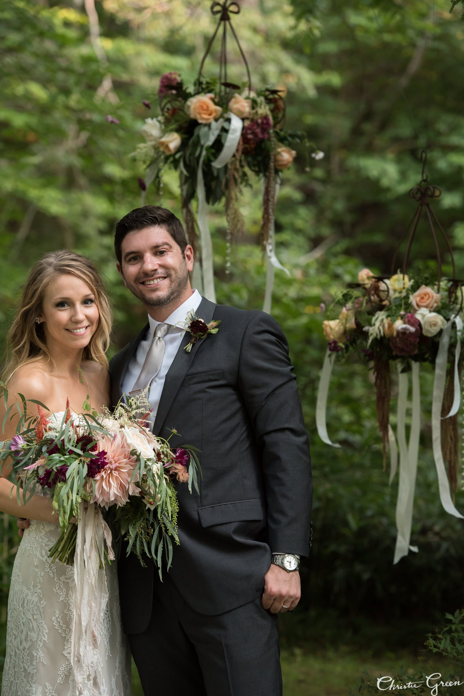 Bride with garden bouquet in Justin Alexander and groom in front of romantic hanging florals. Flowers by Fresh Designs Florist. Photo by Christie Green Photography