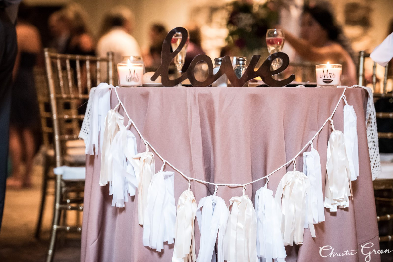 Sweetheart table at Old Mill wedding draped in blush linens and white tassel garland and topped with love sign. Photo by Christie Green Photography