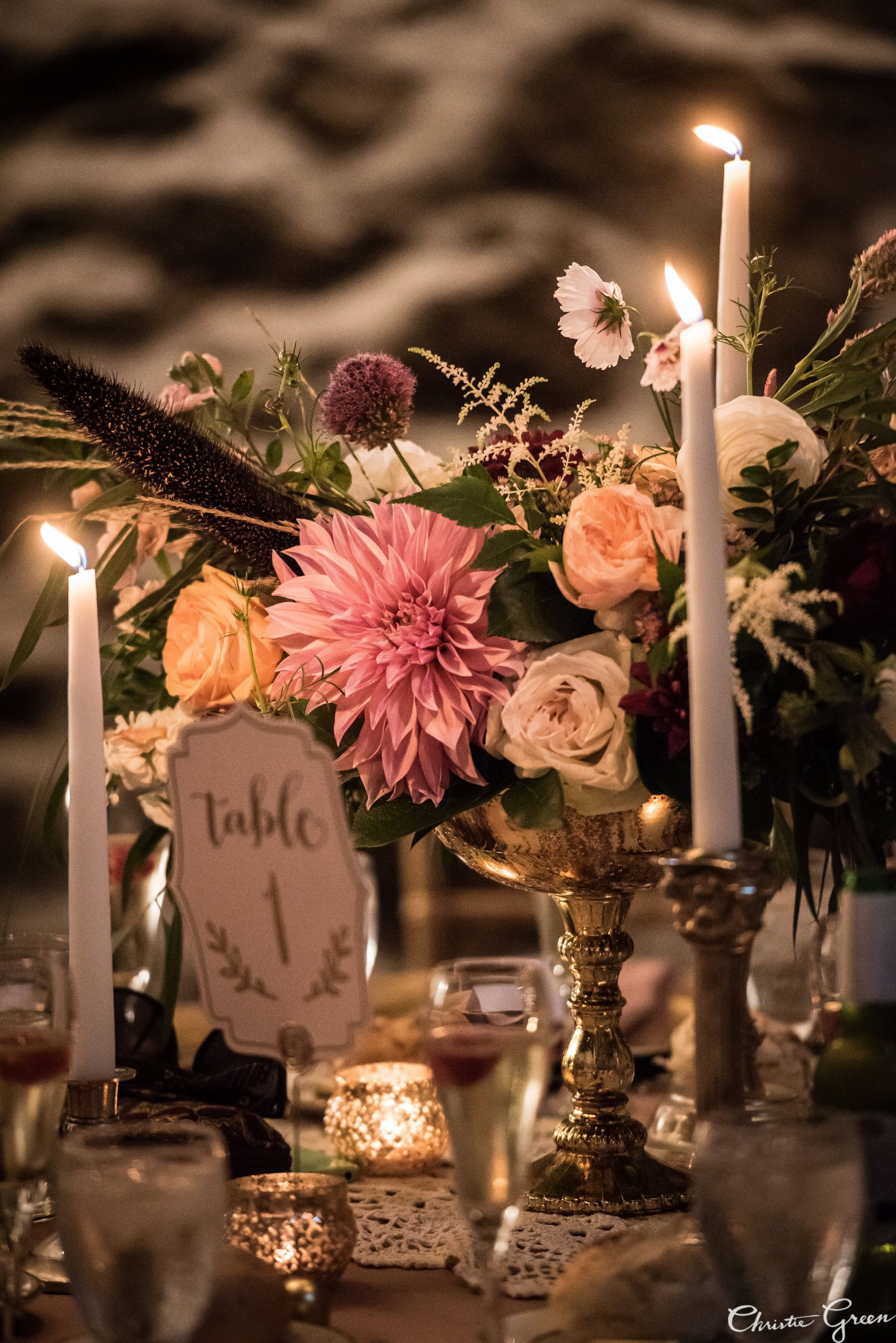 Romantic floral centerpiece in blush, ivory, peach and burgundy by Fresh Designs Florist surrounded by taper candles and tea lights. Photo by Christie Green Photography