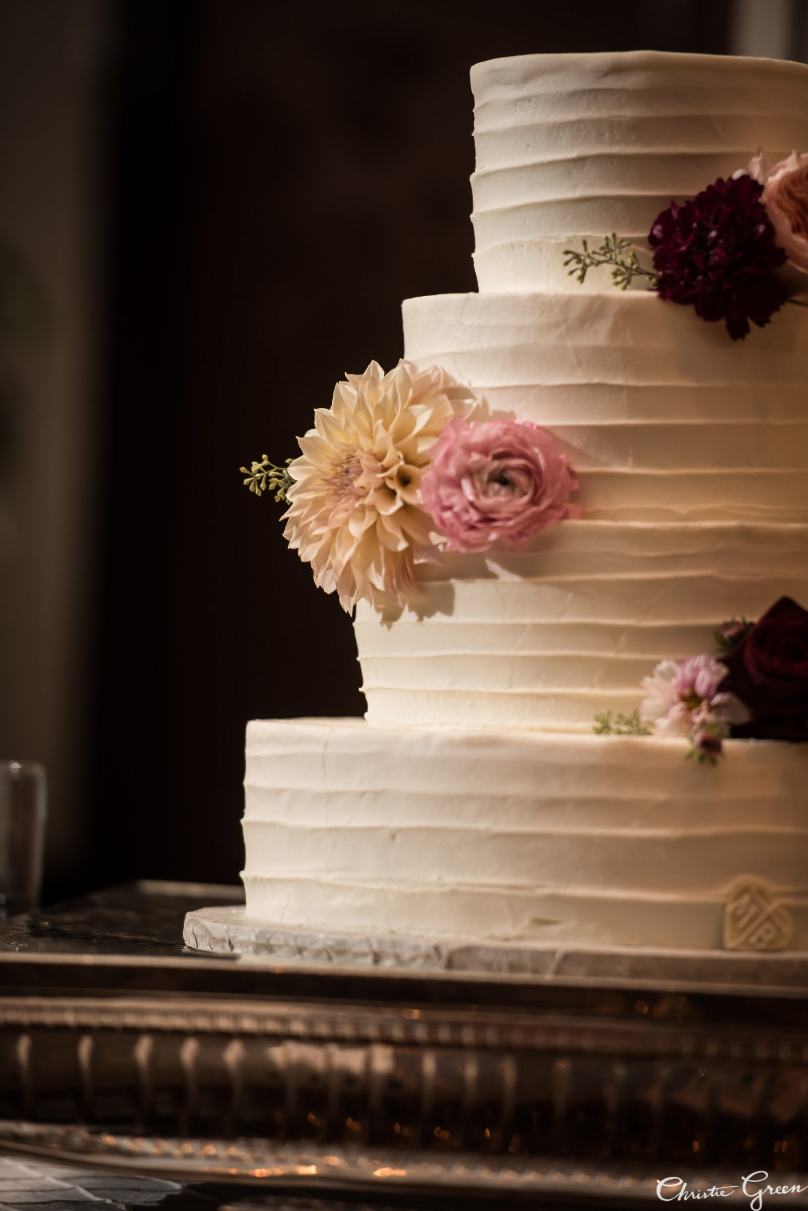 Four tier ivory buttercream cake by the Master's Baker topped with fresh flowers in blush, peach, and burgundy by Fresh Designs Florist. Photo by Christie Green Photography