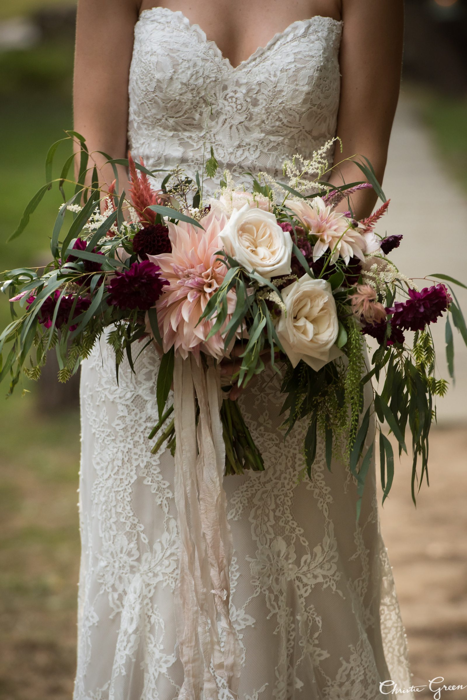 Bride in lace Justin Alexander gown holding stunning summer bridal bouquet filled with dahlias and roses by Fresh Designs Florist. Photo by Christie Green Photography
