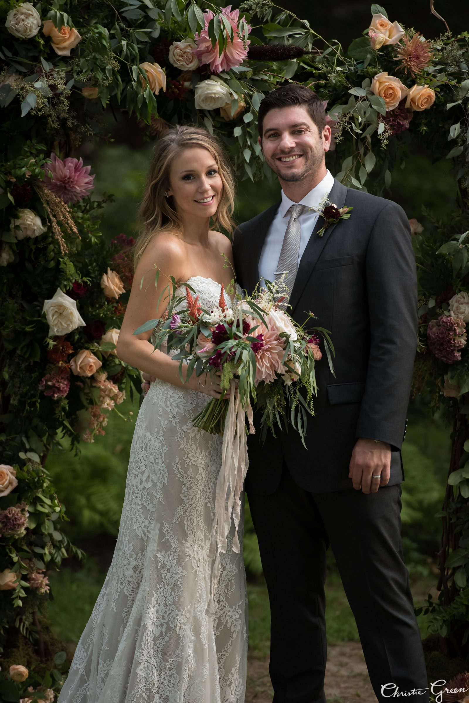 Bride in Justin Alexander and groom in front of romantic floral arch. Flowers by Fresh Designs Florist. Photo by Christie Green Photography