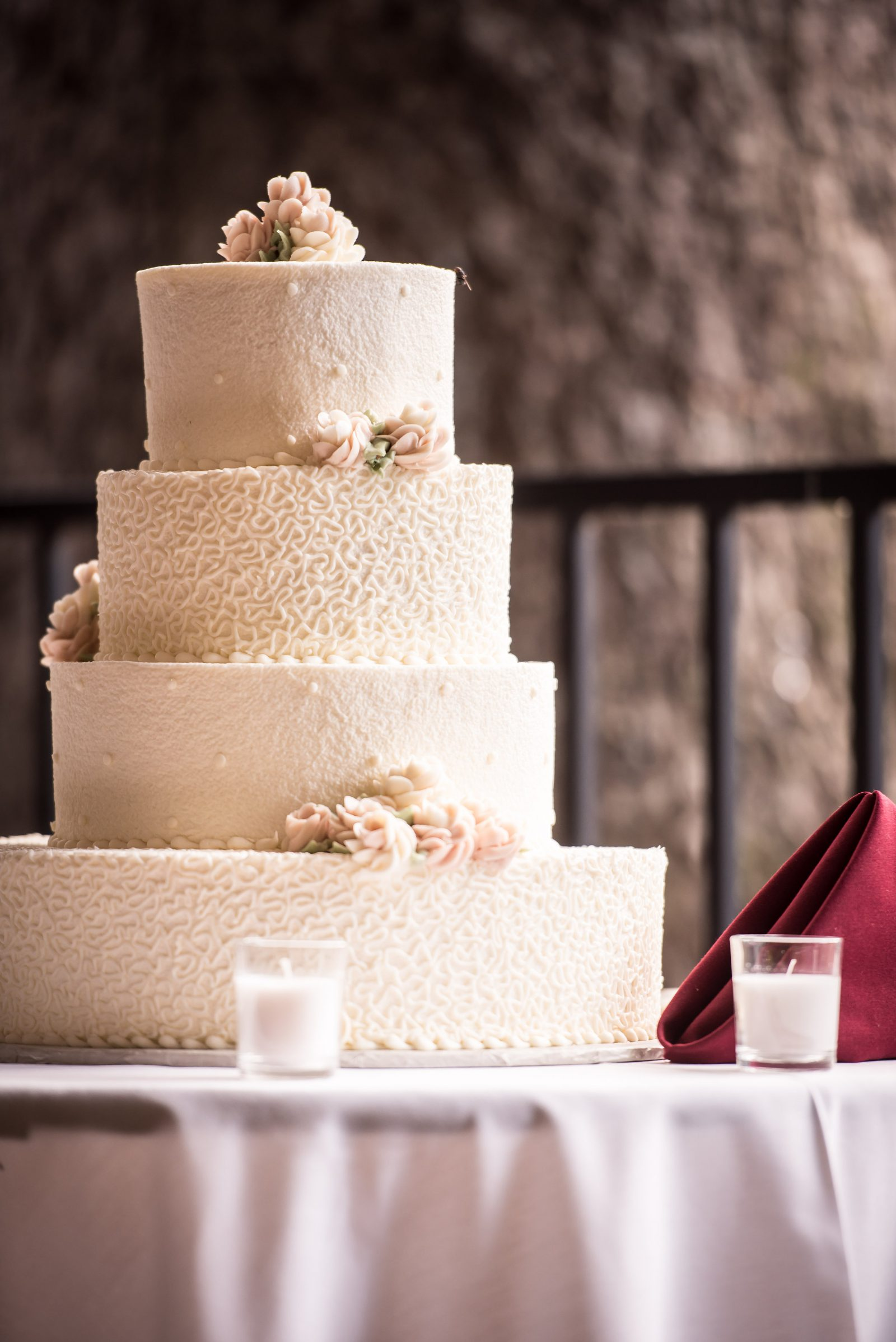 Four tiered ivory wedding cake with different textures on each tier and sugar flowers by The Master's Baker. Photo by Christie Green Photography