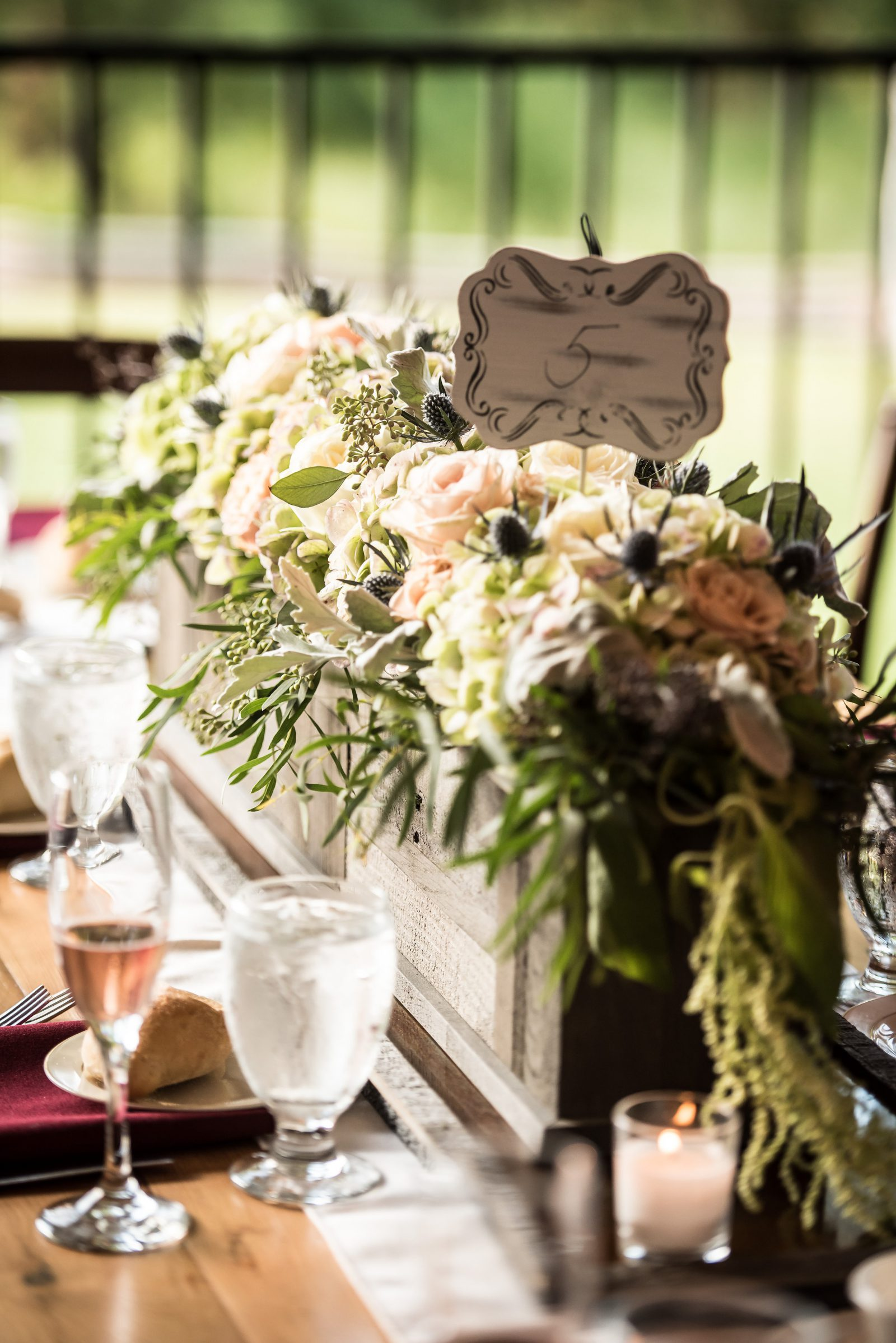 Rustic wooden planter filled with blush and ivory florals and flowing greenery by The Argyle Bouquet and table number sign. Photo by Christie Green Photography