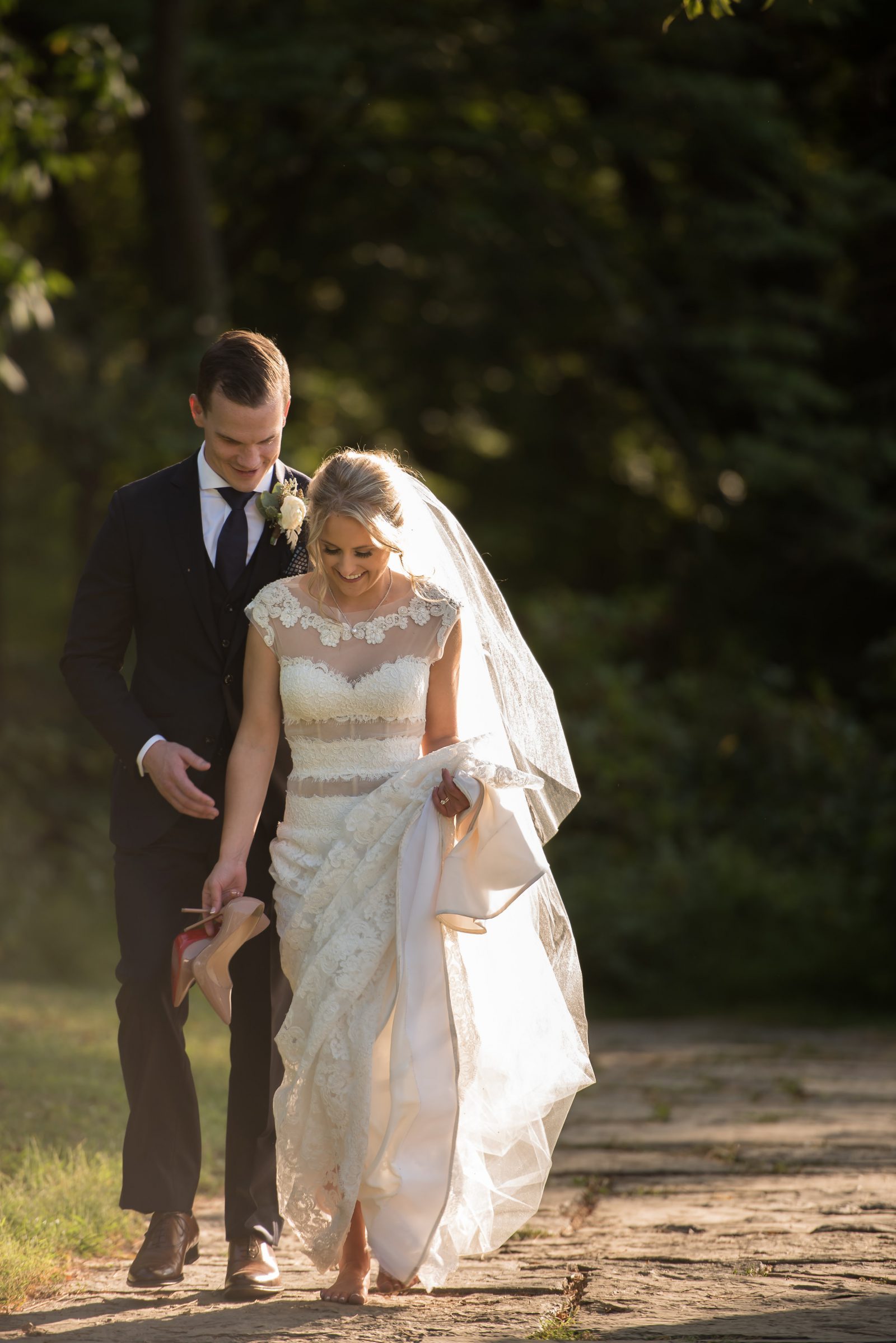 Groom and barefoot bride holding her Louboutins walk along path at Philander Chase Knox Estate during wedding portraits. Photo by Christie Green Photography