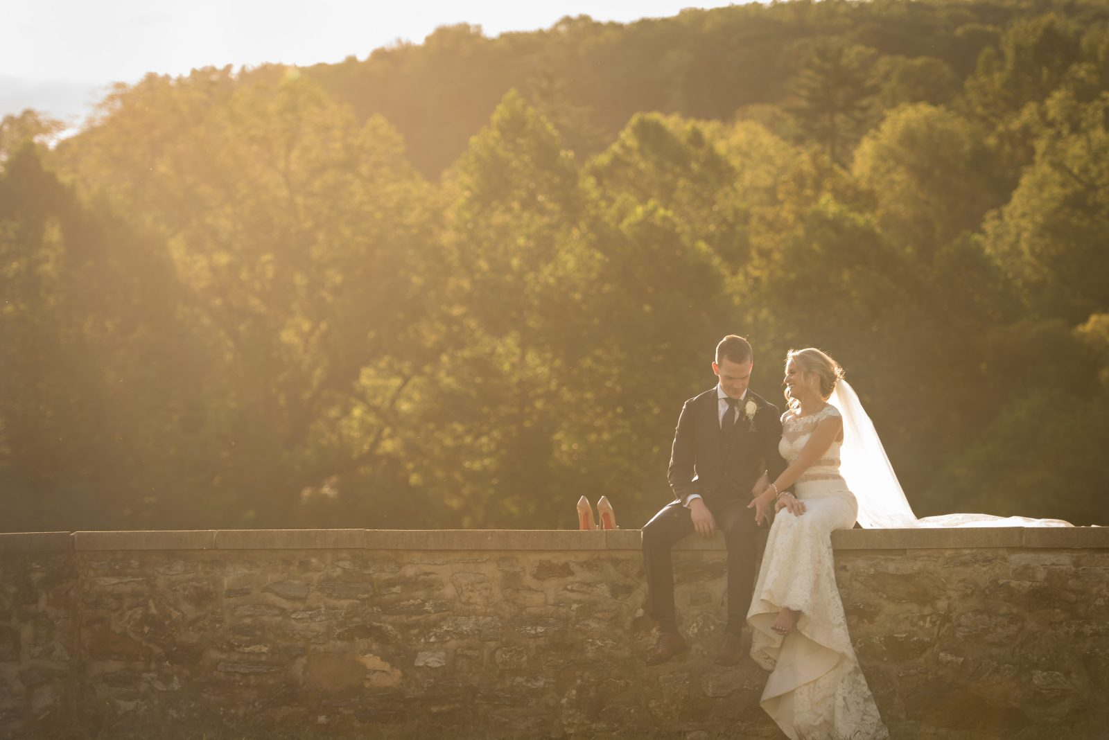 Sunset portrait of bride and groom sitting on a stone wall at Philander Chase Knox Estate. Photo by Christie Green Photography