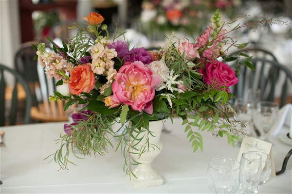 Organic bright centerpiece with peonies and roses in pink and orange hues and flowing greenery by Fresh Designs Florist. Photo by Amy Tucker Photography