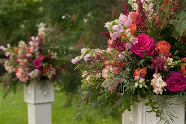 Bright organic ceremony flowers with pink, purple, and orange hues combined with flowing greenery on pedestals by Fresh Designs Florist. Photo by Amy Tucker Photography