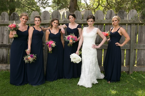 Bride in lace Maggie Sottero gown with her bridesmaids in navy Watters dresses, holding garden bouquets by Fresh Designs Florist. Photo by Amy Tucker Photography
