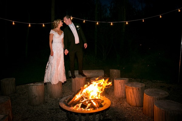 Bride and Groom by Fire Pit at Anthony Wayne House Wedding. Photo by Amy Tucker Photography