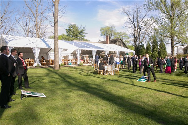 Guests play yard games at a tented Anthony Wayne House Wedding reception. Photo by Amy Tucker Photography