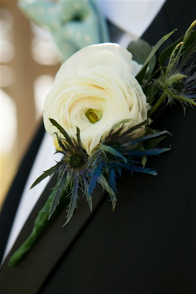 White ranunculus boutonniere with blue thistle accents by Alfred of Philadelphia. Photo by Amy Tucker Photography