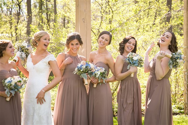 Bride laughs with her bridesmaids in latte Bill Levkoff gowns, carrying spring garden bouquets by Alfred of Philadelphia. Photo by Amy Tucker Photography