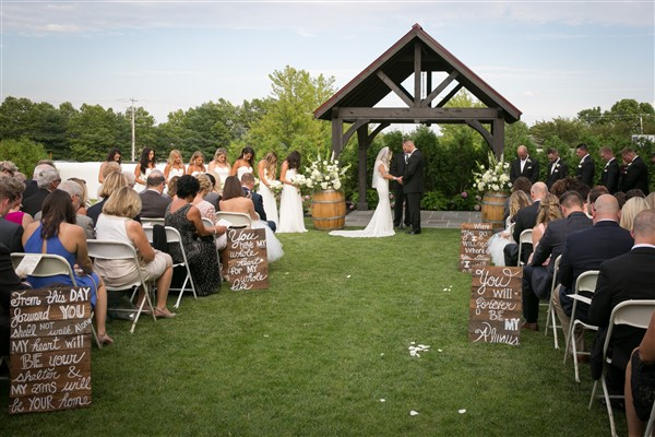 Outdoor summer wedding ceremony at Normandy Farm Hotel, with hand-painted signs along the aisle. Photo by Amy Tucker Photography
