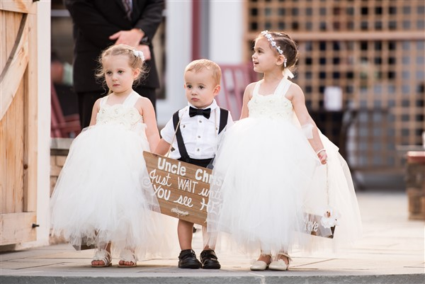 Flower girls wearing tulle gowns are escorted by the tiny suspender-wearing, sign-toting ring bearer down the aisle at a Normandy Farm Wedding. Photo by Amy Tucker Photography