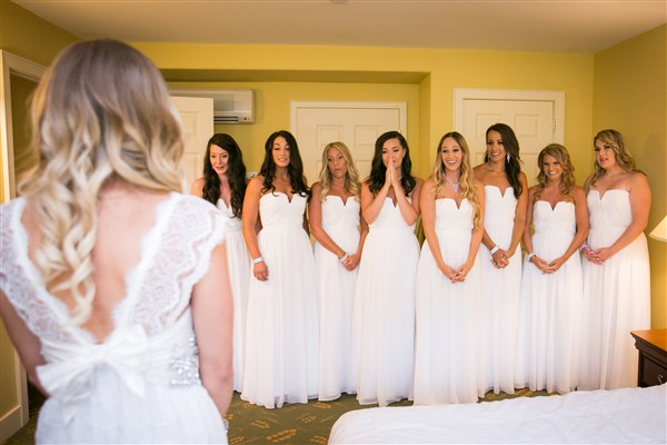 Bride wearing Lovely Bride does a first look with her all-in-white bridesmaids. Photo by Amy Tucker Photography