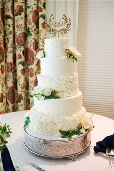 White classic five-tiered wedding cake by Cozze Cakes with fresh flowers and monogrammed topper at Saucon Valley Country Club wedding. Photo by Alexandra Whitney Living