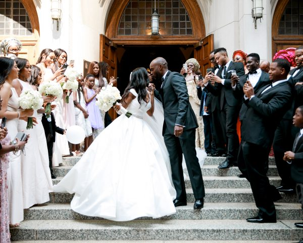 Wedding Couple Kising on Church Steps with Crowd
