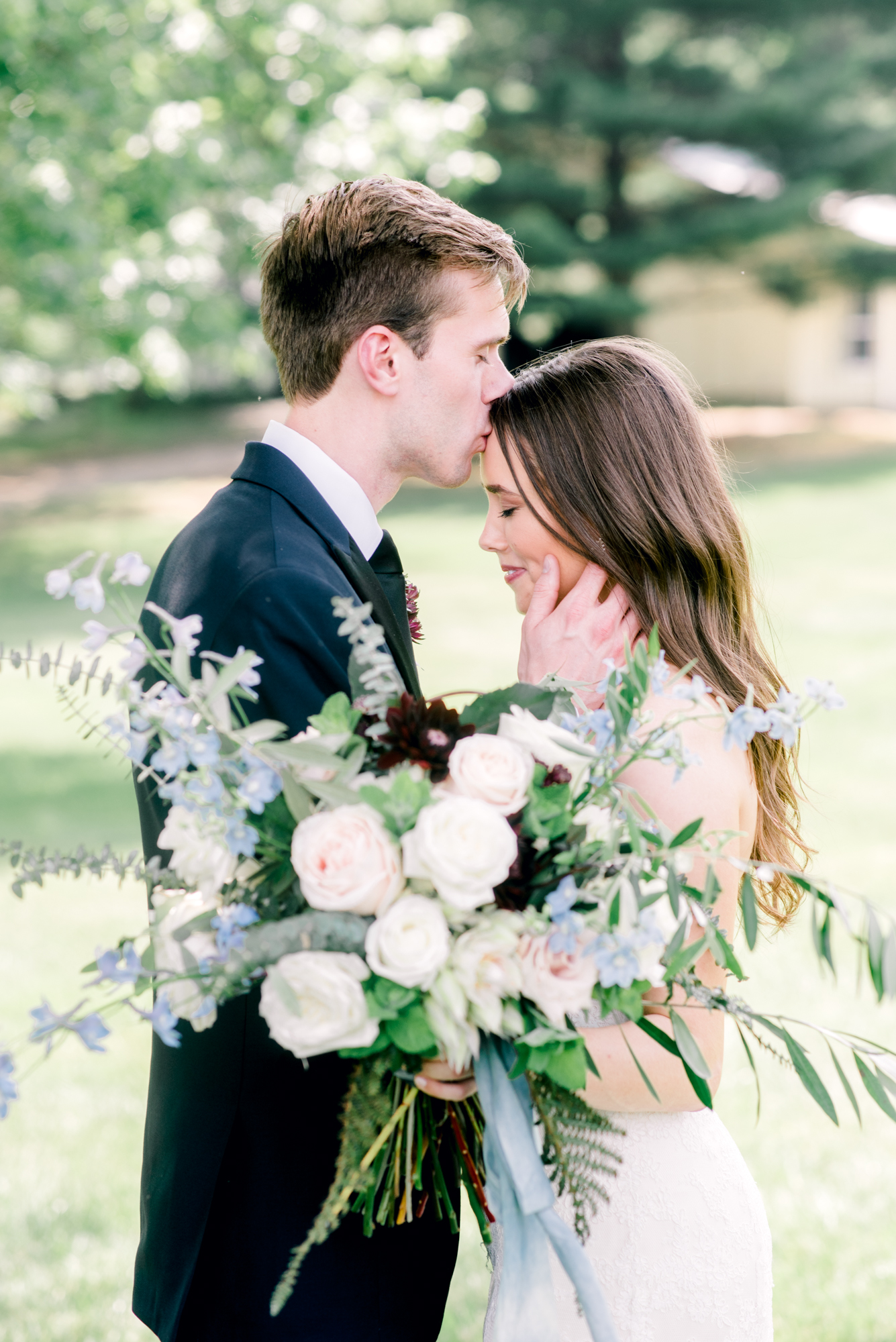 Bride and groom portrait with blue and cream garden bouquet at Oberlin backyard wedding