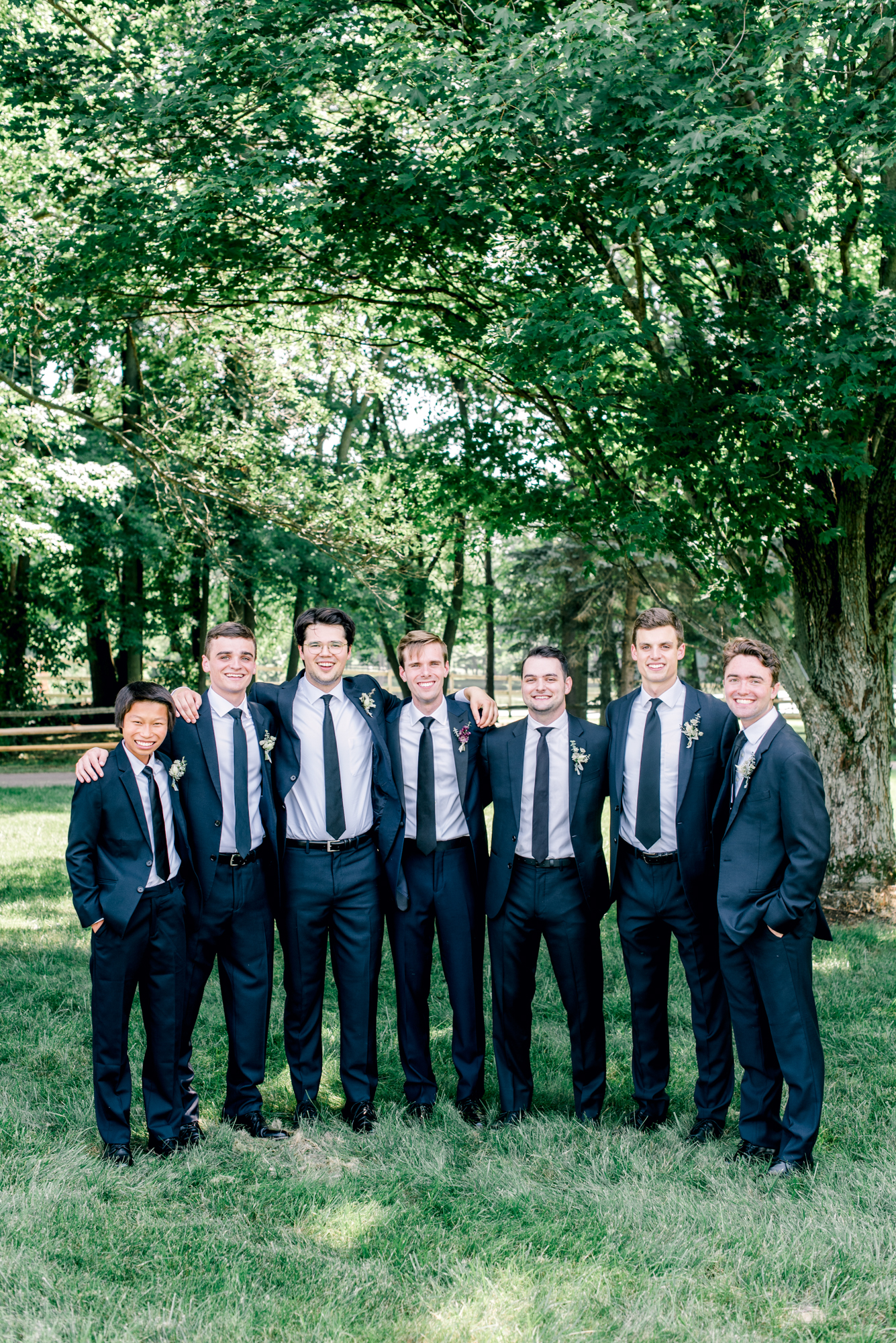 Groom and groomsmen in navy suits with navy ties