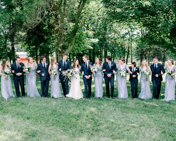 Blue and white bridal party at outdoor summer wedding