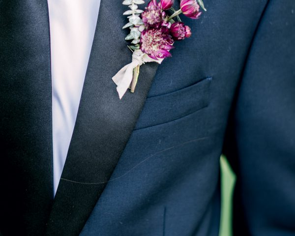 Groom's boutonniere with burgandy flowers and eucalyptus